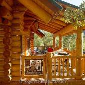 log home front porch with wooden porch swing