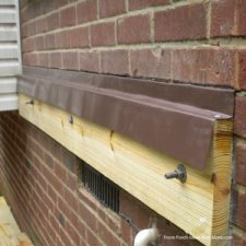 flashing on ledger board attached to brick wall