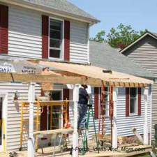 construction workers installing rafters on new front porch