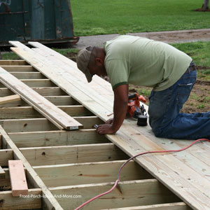 carpenter installing front porch decking material