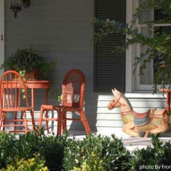 front porch with wooden chairs and rocking horse