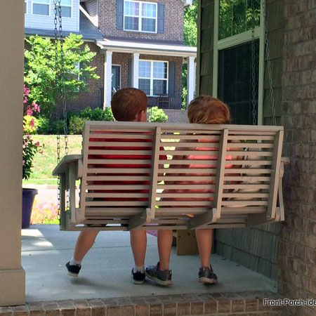 boy and girl swinging on front porch swing