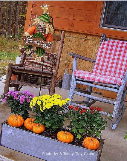 porch decorated for fall with pumpkins and mums