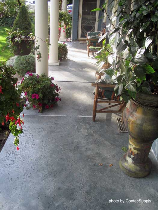 beautifully stained concrete porch floor with planters and seating