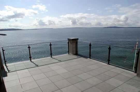 glass deck railings on deck with view of ocean