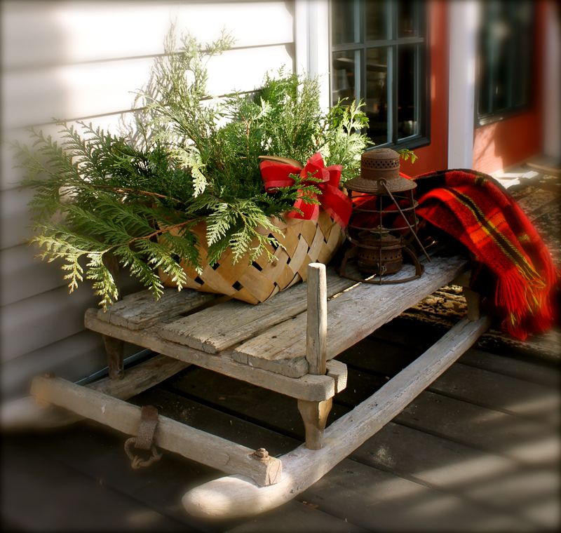 Anita's country porch is decorated with garland and red bows