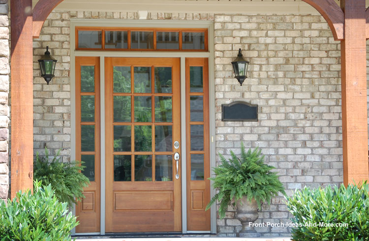 wooden front door with light panels and transom on front porch