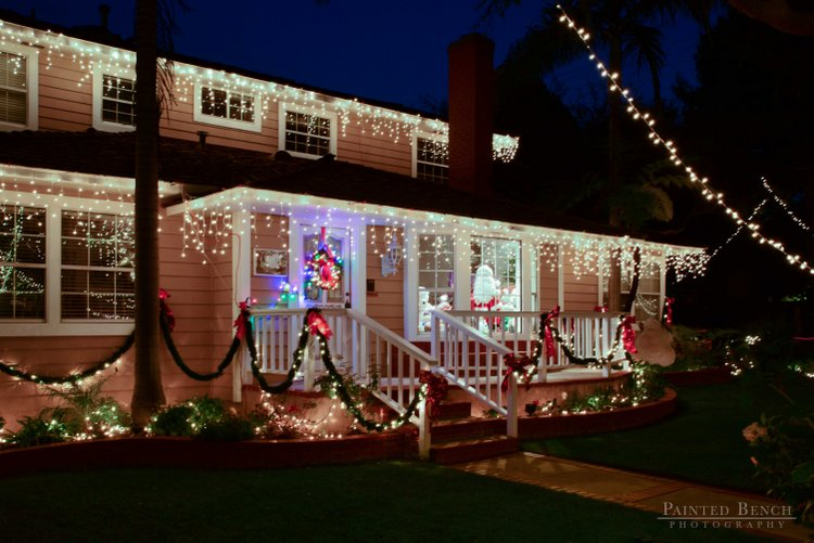 Santa in the window of home with colorful outdoor Christmas lighting
