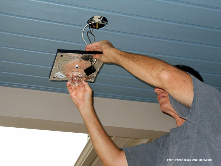 man wiring front porch lights