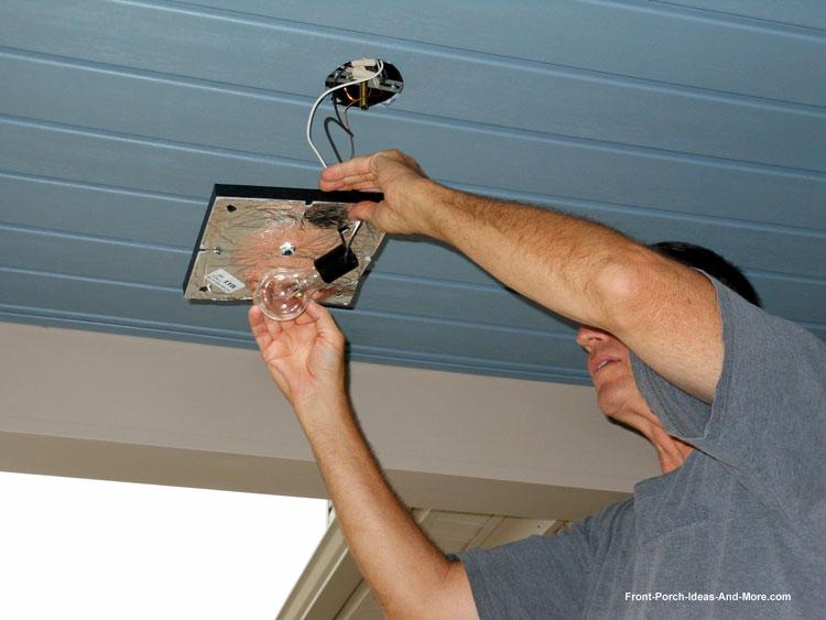 man wiring front porch lights