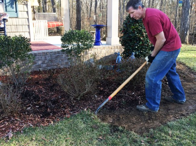 man removing sod in front of porch for gravel walk way