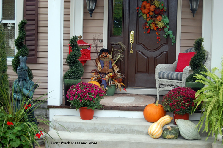 front porch decorated for fall with mums, pumpkins and gourds