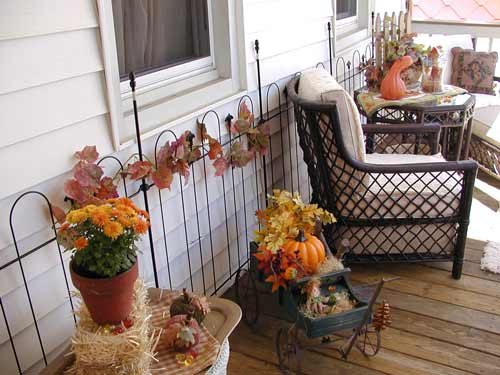 autumn-decorated porch with wire fence backdrop