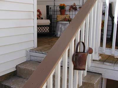 porch railing with watering can attached