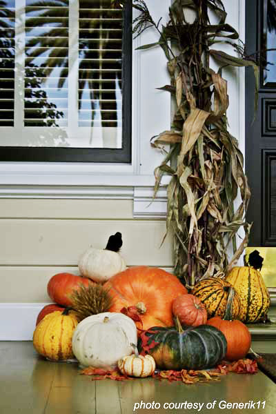 traditional pumpkins and corn stalks on front porch