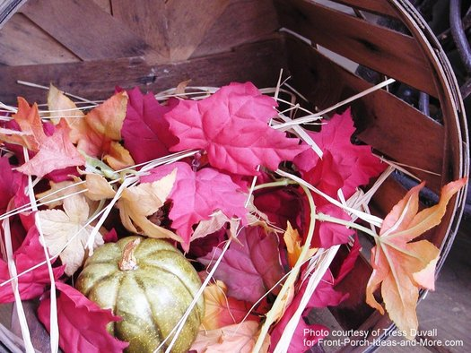 apple basket filled with colorful fall leaves
