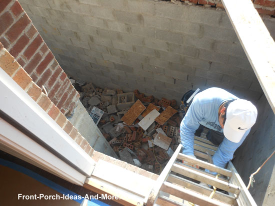 worker descending ladder into front porch cavity