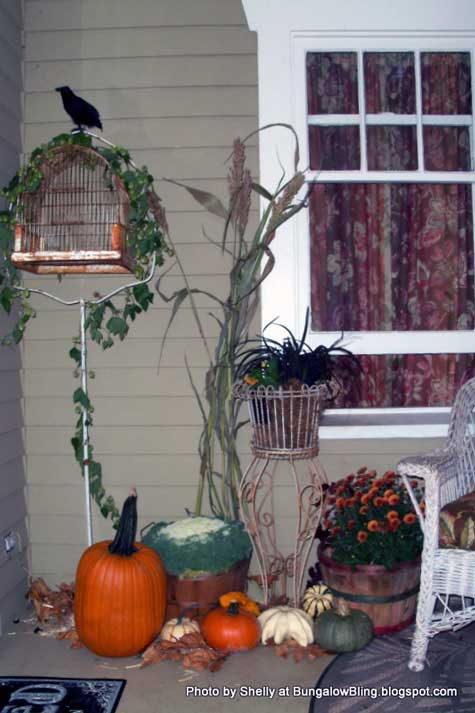 bird cage and pumpkins on porch