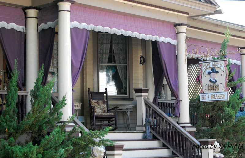 porch curtains adorn Victorian home