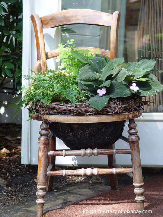 old chair tuned into a planter on porch