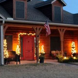 Lodge-like front porch lit for Christmas - Three Mango Seed