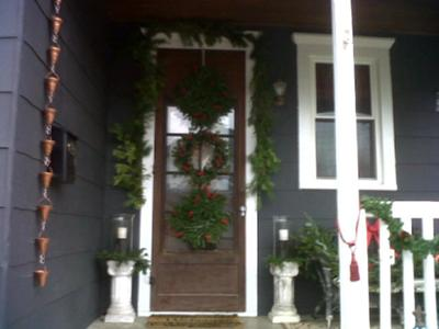 Front door has a set of three wreaths hanging from it.