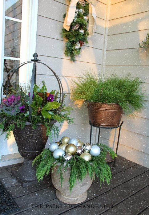 The Painted Chandelier - trio of attractive pots in corner of porch - filled with fresh plants and Christmas sparkle