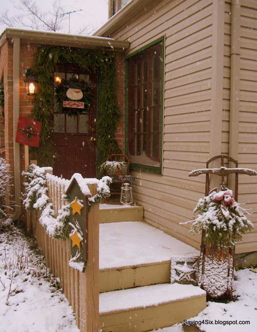 snowy front porch decorated for the holidays