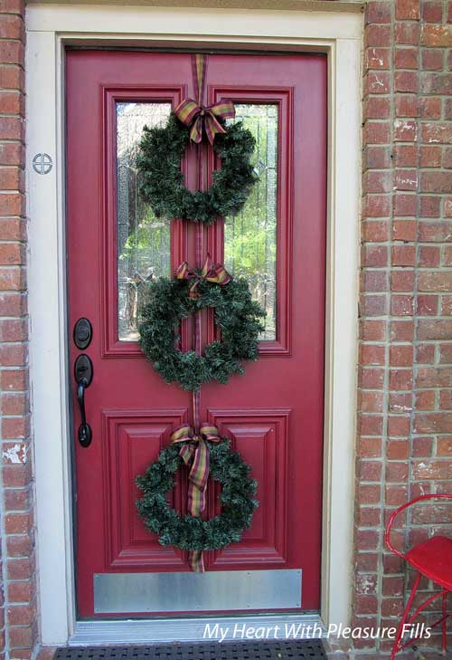 front door with three holiday wreaths