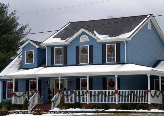 Christmas wreaths decorate the windows of this pretty blue home