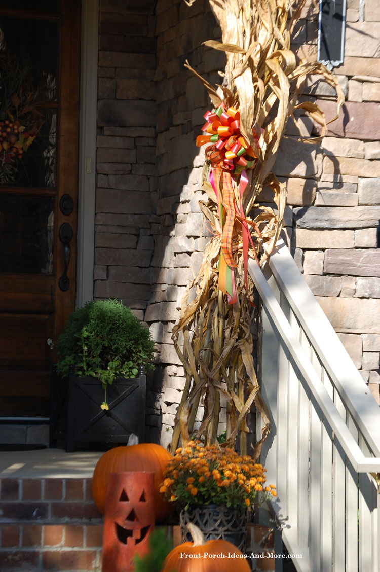 corn stalks for fall on front porch tied with ribbon