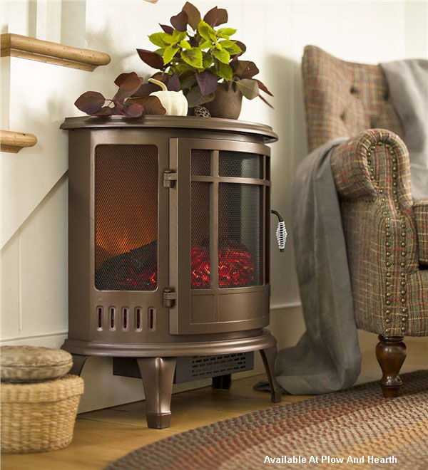 curved electric wood stove beside comfortable chair