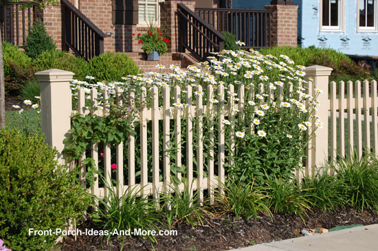 picket fence with beautiful daisies next to front porch