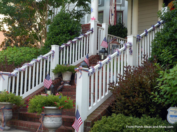 front porch bannister with 4th of July garland