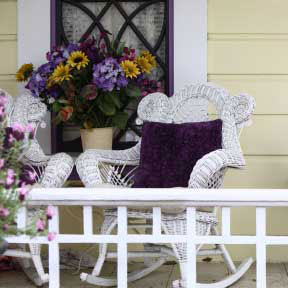 front porch with with vibrant purple colors and white wicker rocking chair