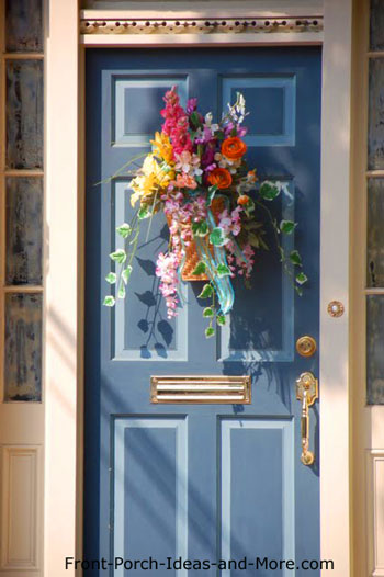 A colorful and cheerful front door wreath on a pretty blue door