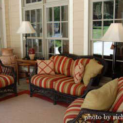 an enclosed porch with luxurious outdoor furniture