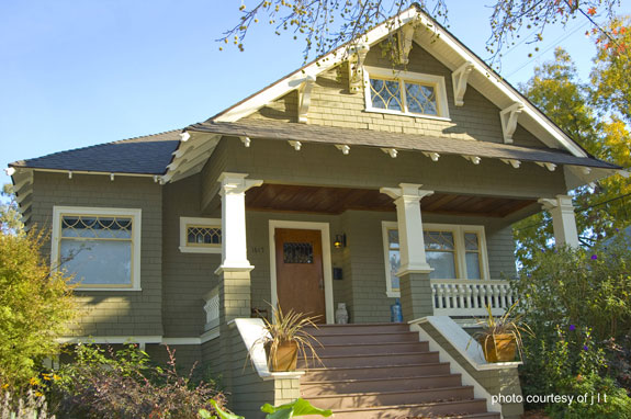 craftsman-style front porch with exposed rafters and eave braces