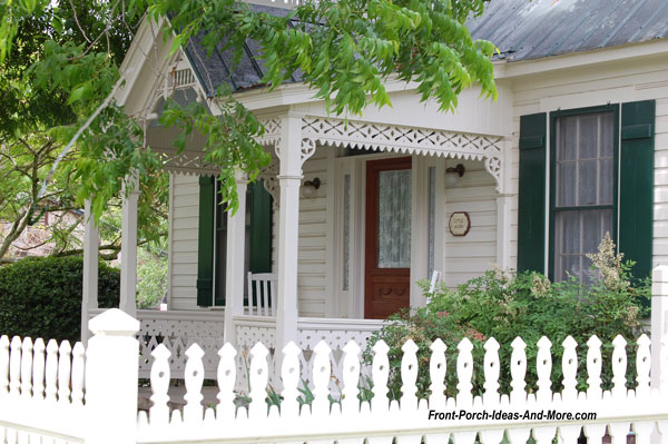 Exterior house trim on small front porch and complementary picket fence
