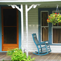 wooden screen door on front porch with rocking chairs
