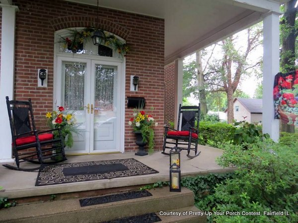 Black rocking chairs and gorgeous flowers on this wraparound porch