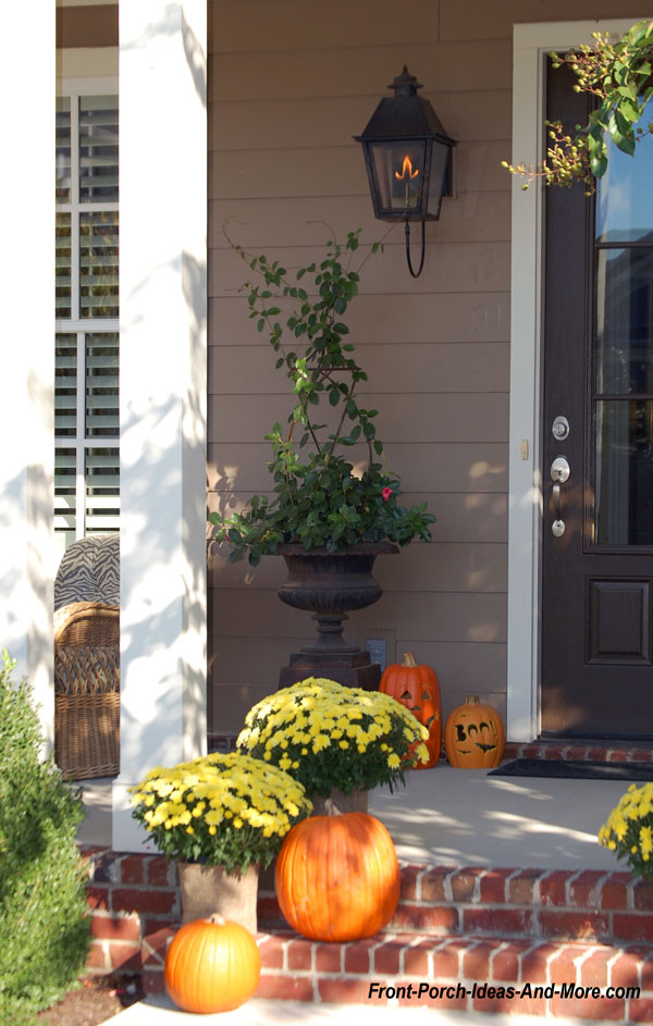 yellow mums and pumpkins with autumn door wreath on front porch