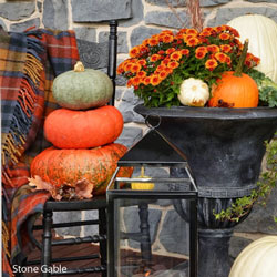fall display with lantern, blanket, and pumpkins