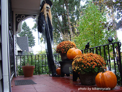 fall and halloween display on front porch including crows, witch and mums
