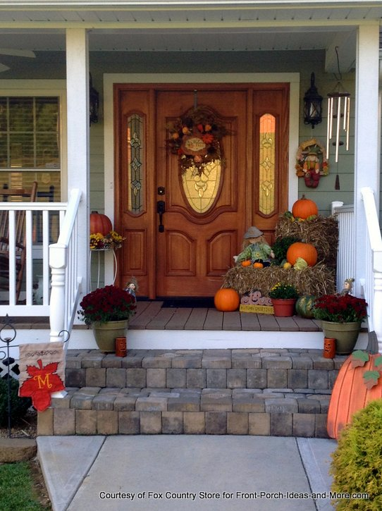 gorgeous wooden front door and fall decorations on front porch