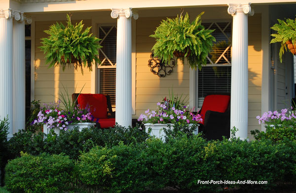 summer front porch with red cushions and hanging ferns