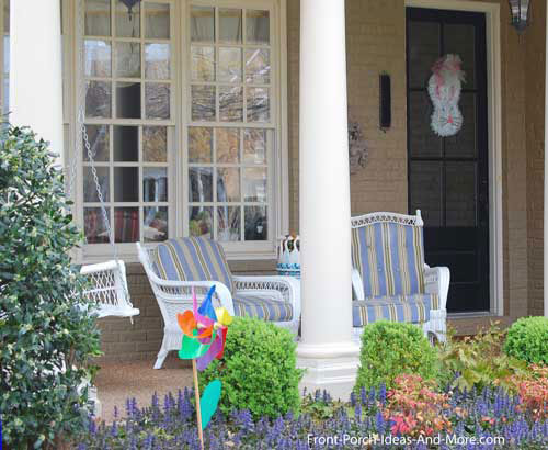 wicker furniture with colorful cushions on front porch