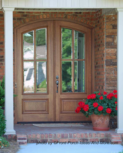 Wooden Exterior Front Doors With Curved Tops And Pot Of Geraniums To The  Side Part 97