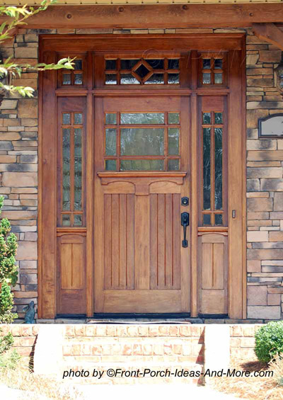 wooden exterior front doors with curved tops and pot of geraniums to the side