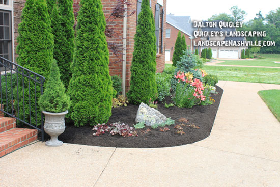 nicely landscaped walkway leading from porch to driveway